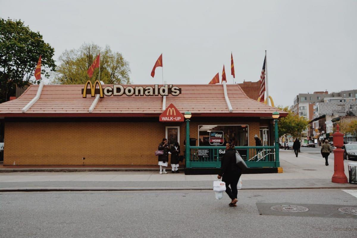 woman walking towards McDonald's branch during daytime